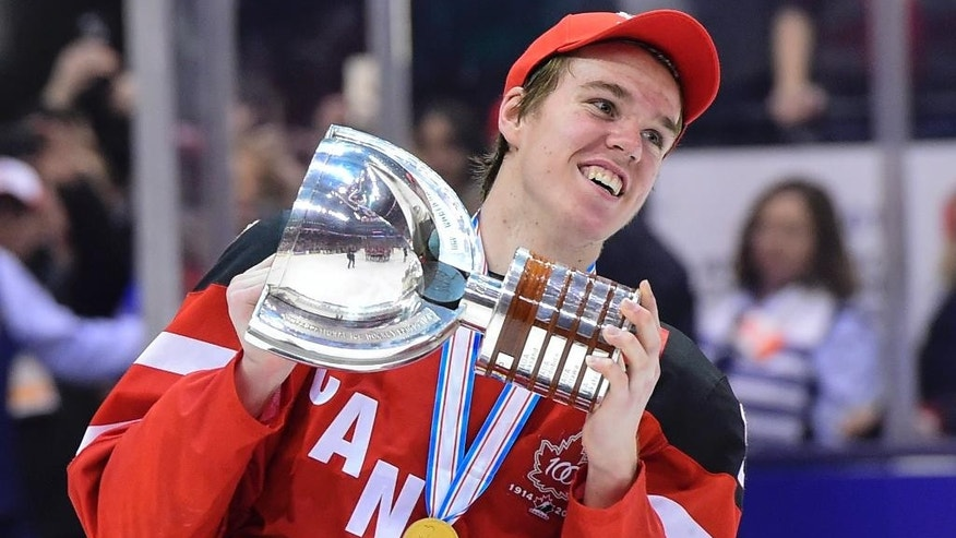 FILE - In this Jan. 5, 2015, file photo, Canada's Connor McDavid skates with the trophy following his team's 5-4 win over Russia in the title game at the hockey World Junior Championship in Toronto. The Edmonton Oilers have won the NHL draft lottery and the right to select McDavid first overall. (Frank Gunn/The Canadian Press via AP, File) MANDATORY CREDIT