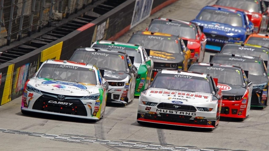 Driver Erik Jones (20) leads Joey Logano (22) and the rest of the field to start during a NASCAR Xfinity Series auto race at Bristol Motor Speedway on Saturday, April 18, 2015, in Bristol, Tenn. (AP Photo/Wade Payne)