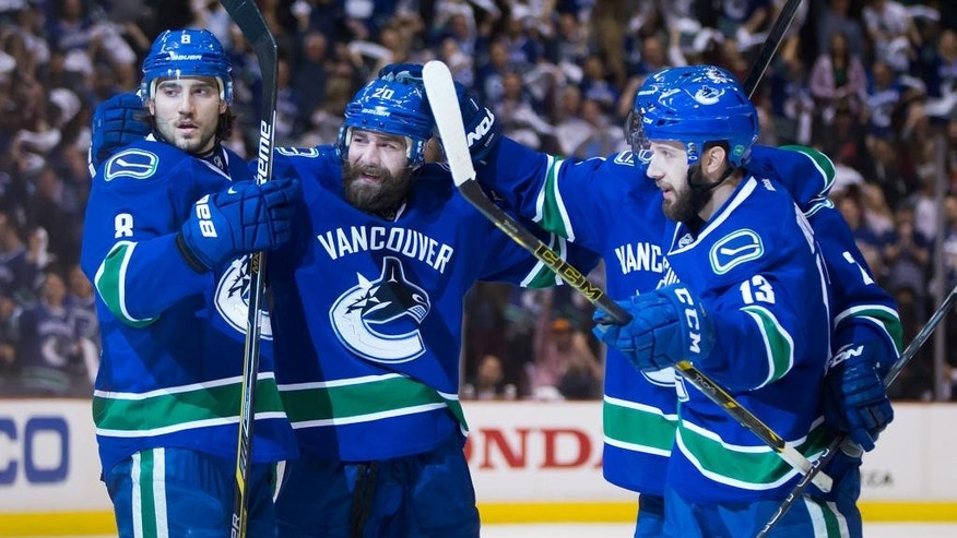 Vancouver Canucks' Chris Tanev, Chris Higgins, Nick Bonino and Dan Hamhuis, back right, celebrate Higgins' goal against the Calgary Flames during the first period of Game 2 of an NHL hockey first-round playoff series, Friday, April 17, 2015, in Vancouver, British Columbia. (Darryl Dyck/The Canadian Press via AP)