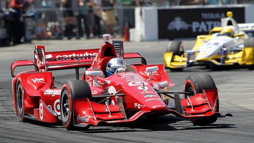 Scott Dixon (9), of New Zealand, drives through a turn in front of Simon Pagenaud (22), of France, on his way to winning the IndyCar Toyota Grand Prix of Long Beach auto race on Sunday, April 19, 2015, in Long Beach, Calif. (AP Photo/Alex Gallardo)