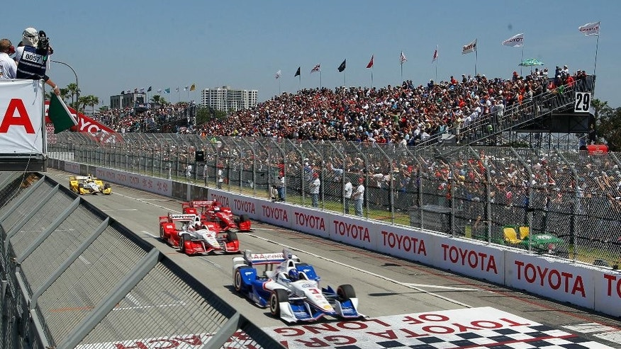 Helio Castroneves (3), of Brazil, takes the lead to start the IndyCar Toyota Grand Prix of Long Beach auto race in front of Juan Pablo Montoya (2), of Colombia, and Scott Dixon (9), of New Zealand, Sunday, April 19, 2015, in Long Beach, Calif. Scott Dixon won the race. (AP Photo/Alex Gallardo)