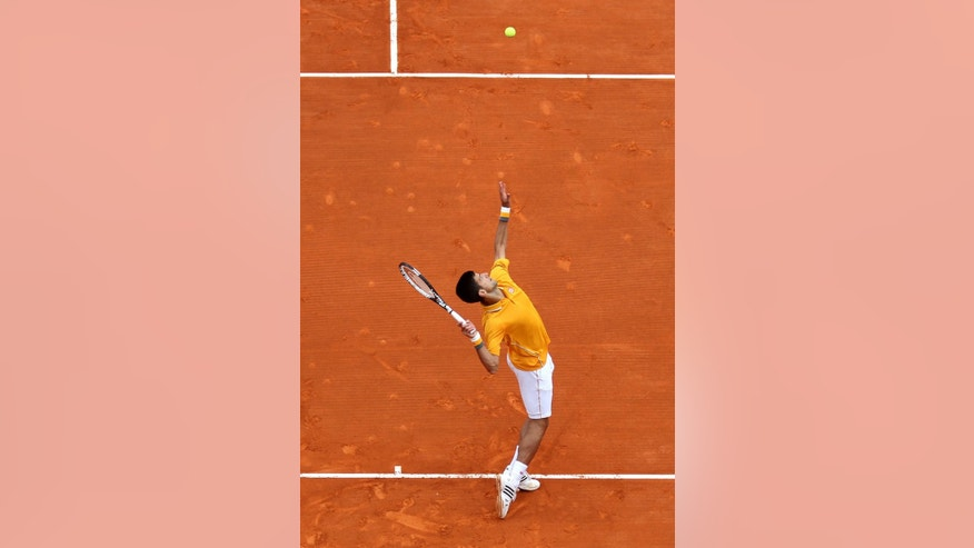 Novak Djokovic of Serbia serves the ball to Thomas Berdych of Czech Republic during their final match of the Monte Carlo Tennis Masters tournament in Monaco, Sunday, April 19, 2015. (AP Photo/Lionel Cironneau)