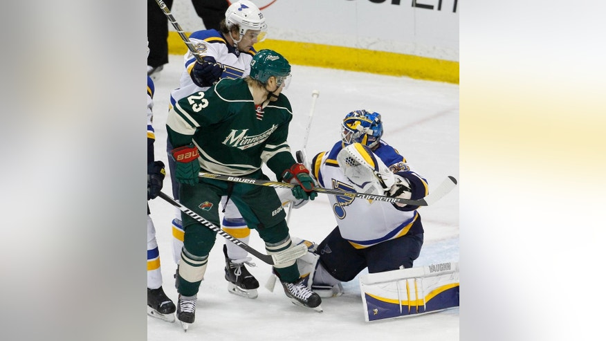 St. Louis Blues goalie Jake Allen, right, deflects a shot in front of Minnesota Wild left wing Sean Bergenheim (23), of Finland, and Blues defenseman Kevin Shattenkirk, left rear, during the first period of Game 3 of an NHL hockey first-round playoff series game in St. Paul, Minn., Monday, April 20, 2015. (AP Photo/Ann Heisenfelt)