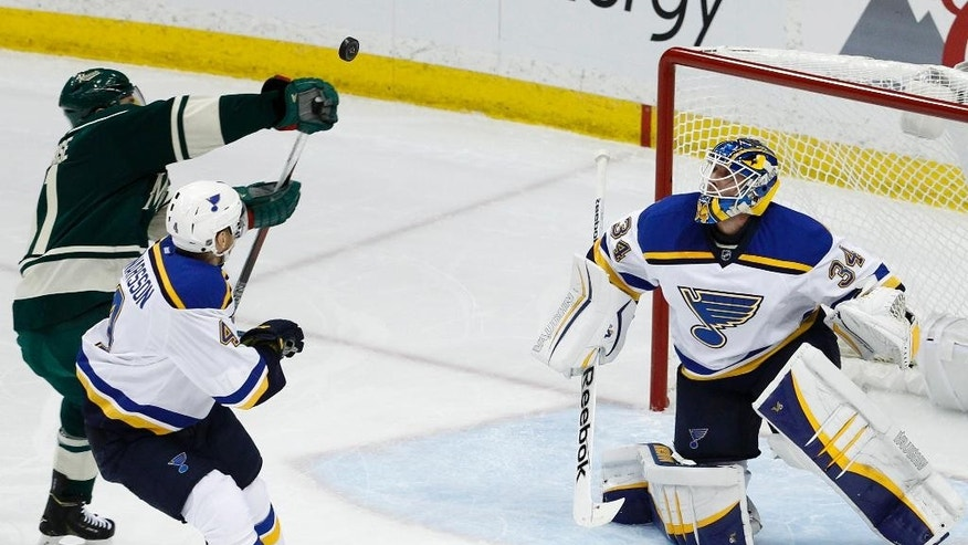 St. Louis Blues goalie Jake Allen (34) deflects a shot back toward Minnesota Wild left wing Zach Parise, left, and Blues defenseman Carl Gunnarsson, center, of Sweden, during the first period of Game 3 of an NHL hockey first-round playoff series game in St. Paul, Minn., Monday, April 20, 2015. (AP Photo/Ann Heisenfelt)