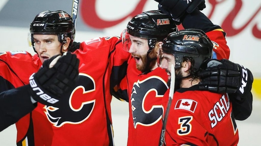 Calgary Flames TJ Brodie, center, celebrates his goal with teammates during first period NHL first round playoff hockey action against the Vancouver Canucks in Calgary, Alberta, Sunday, April 19, 2015. (Jeff McIntosh/The Canadian Press via AP)   MANDATORY CREDIT