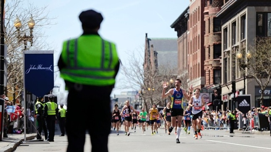 FILE - In this April 21, 2014 file photo, a Boston Police officer stands near the finish line as runners approach during the 118th Boston Marathon in Boston. (AP Photo/Robert F. Bukaty, File)