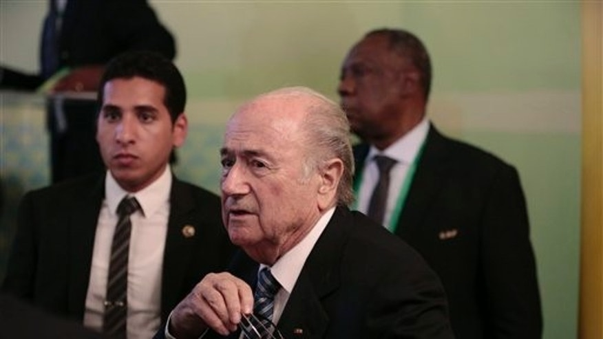 FIFA President Sepp Blatter, center, and Confederation of African Football President Issa Hayatou, back right, leave a press conference in Cairo, Egypt, Tuesday, April 7, 2015.