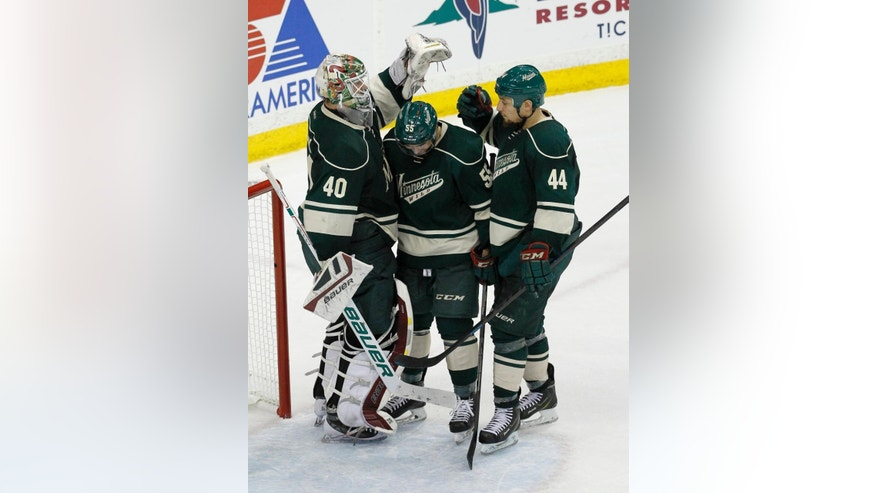 Minnesota Wild goalie Devan Dubnyk (40) celebrates with defenseman Matt Dumba, center, and right wing Chris Stewart (44) after the Wild defeated the St. Louis Blues 3-0 in Game 3 of an NHL hockey first-round playoff series game in St. Paul, Minn., Monday, April 20, 2015. (AP Photo/Ann Heisenfelt)