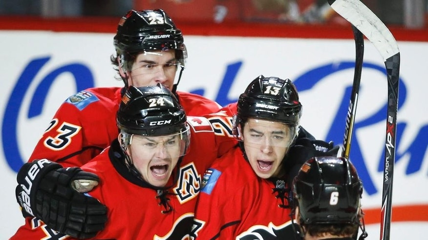 Calgary Flames' Johnny Gaudreau, center right, celebrates his goal with against the Vancouver Canucks with teammates Sean Monahan, left, Jiri Hudler, center left, from the Czech Republic and Dennis Wideman during the first period of Game 4 of a first-round NHL hockey playoff series, Tuesday, April 21, 2015, in Calgary, Alberta. (Jeff McIntosh/The Canadian Press via AP)