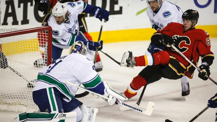 Vancouver Canucks goalie Eddie Lack, front left, protects the net as Calgary Flames' Sam Bennett gets hauled down in front of him during the first period of Game 4 of a first-round NHL hockey playoff series, Tuesday, April 21, 2015, in Calgary, Alberta. (Jeff McIntosh/The Canadian Press via AP)