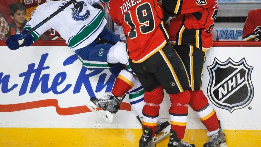 Vancouver Canucks' Luca Sbisa, left, from Italy, is checked by Calgary Flames' Michael Ferland, right, and David Jones during the first period of Game 4 of a first-round NHL hockey playoff series, Tuesday, April 21, 2015, in Calgary, Alberta. (Jeff McIntosh/The Canadian Press via AP)