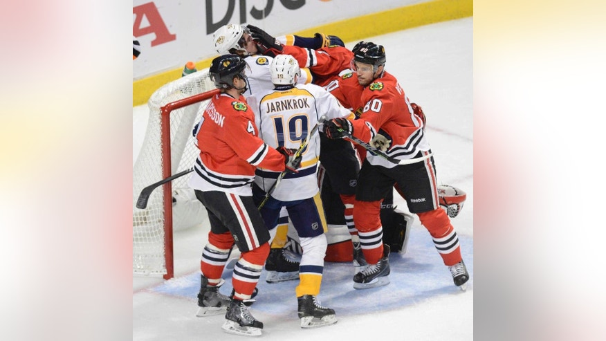 Chicago Blackhawks and Nashville Predators players shove each other in the Chicago net late in the second period  in Game 4 of an NHL Western Conference hockey playoff series against the Nashville Predators on Tuesday, April 21, 2015, in Chicago. (Daily Herald/John Starks via AP)