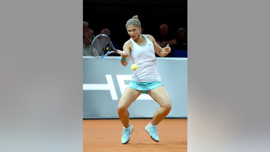 Sara Errani of Italy returns the ball to Agnieszka Radwanska of Poland in the first round of the Porsche Grand Prix tennis tournament in Stuttgart, Germany, Wednesday, April 22, 2015. (Marijan Murat/dpa via AP)