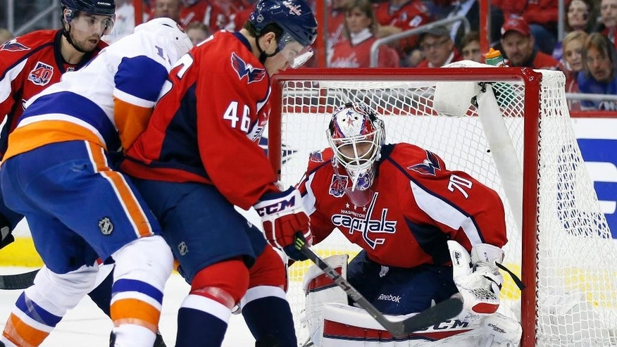 Washington Capitals center Michael Latta (46) blocks New York Islanders left wing Matt Martin (17) away from the puck with goalie Braden Holtby (70) in goal, during the second period of Game 5 in the first round of the NHL hockey Stanley Cup playoffs, Thursday, April 23, 2015, in Washington. (AP Photo/Alex Brandon)