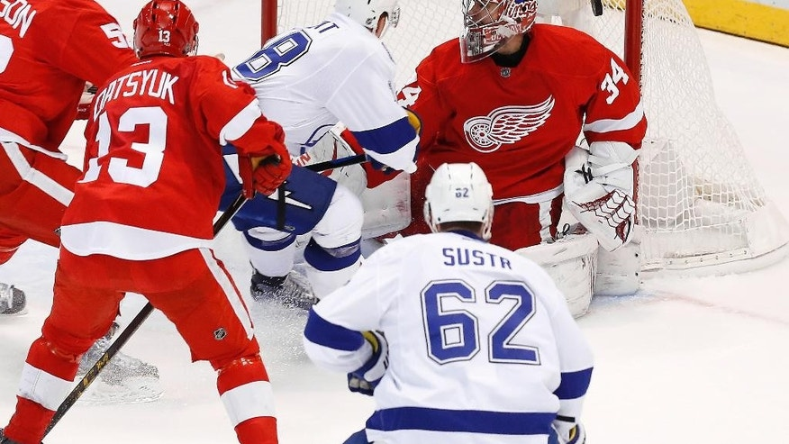 Tampa Bay Lightning left wing Ondrej Palat (18) scores on Detroit Red Wings goalie Petr Mrazek (34) during the third period of Game 4 of a first-round NHL Stanley Cup hockey playoff series Thursday, April 23, 2015, in Detroit. (AP Photo/Paul Sancya)