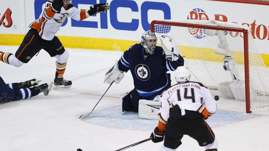 Anaheim Ducks' Emerson Etem (16) scores on Winnipeg Jets goaltender Ondrej Pavelec (31) as Ducks' Tomas Fleischmann (14) watches during the first period of Game 4 of a first-round NHL hockey playoff series, Wednesday, April 22, 2015, in Winnipeg, Manitoba. (John Woods/The Canadian Press via AP)