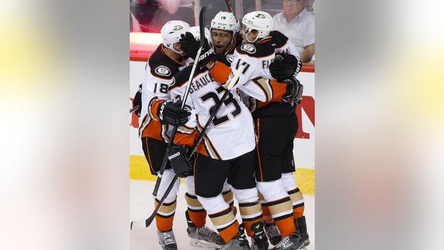 Anaheim Ducks' Tim Jackman (18), Francois Beauchemin (23), Emerson Etem (16) and Tomas Fleischmann (14) celebrate Etem's goal against the Winnipeg Jets during the first period of Game 4 of a first-round NHL hockey playoff series, Wednesday, April 22, 2015, in Winnipeg, Manitoba. (John Woods/The Canadian Press via AP)