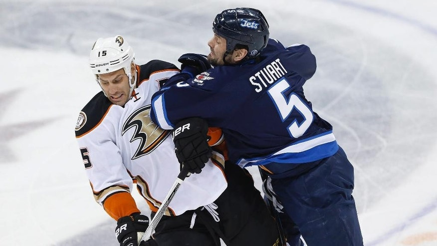 Winnipeg Jets' Mark Stuart (5) hits Anaheim Ducks' Ryan Getzlaf (15) during the first period of Game 4 of a first-round NHL hockey playoff series, Wednesday, April 22, 2015, in Winnipeg, Manitoba. (John Woods/The Canadian Press via AP)
