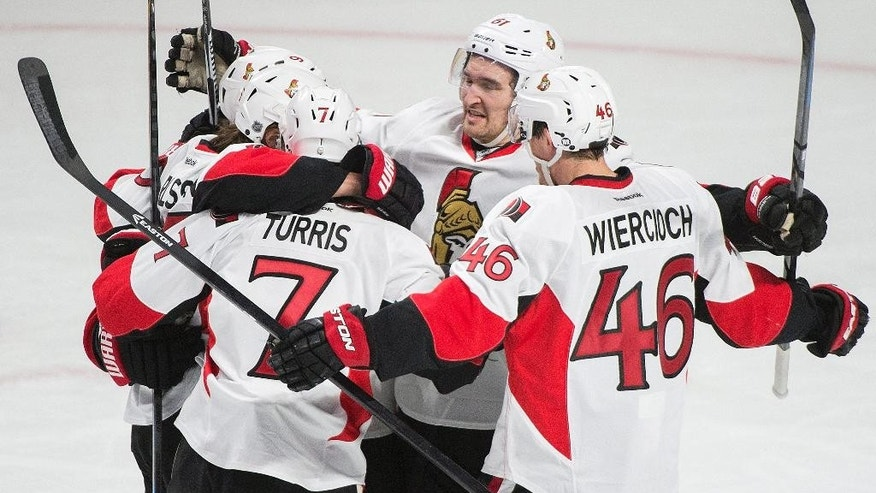 Ottawa Senators' Erik Karlsson, second from left, celebrates with teammates Milan Michalek (9), Kyle Turris (7), Patrick Wiercioch (46) and Mark Stone (61) after scoring against the Montreal Canadiens during the second period of Game 5 of a first-round NHL hockey playoff series, Friday, April 24, 2015, in Montreal. (Graham Hughes/The Canadian Press via AP)