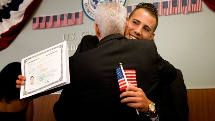Miami Marlins pitcher Jose Fernandez, right, hugs Ralph Fernandez after becoming a U.S. citizen during a naturalization ceremony Friday, April 24, 2015, in Miami. (AP Photo/J Pat Carter)