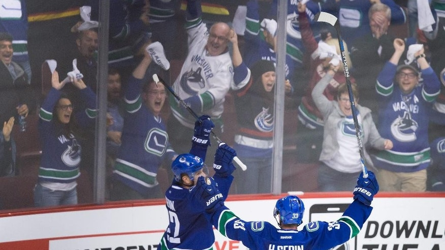 Vancouver Canucks' Daniel Sedin, left, celebrates his goal against the Calgary Flames with his twin brother, Henrik Sedin, during the third period of Game 5 of an NHL hockey first-round playoff series, Thursday, April 23, 2015, in Vancouver, British Columbia. (Darryl Dyck/The Canadian Press via AP)