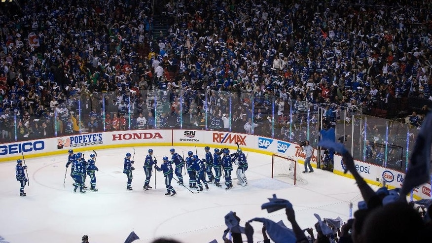 The Vancouver Canucks celebrate after defeating the Calgary Flames 2-1 in Game 5 of an NHL hockey first-round playoff series, Thursday, April 23, 2015, in Vancouver, British Columbia. (Darryl Dyck/The Canadian Press via AP)