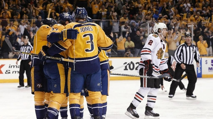 Chicago Blackhawks defenseman Duncan Keith (2) skates to the bench as Nashville Predators celebrate a goal by Colin Wilson (33) during the third period of Game 5 of an NHL hockey first-round playoff series Thursday, April 23, 2015, in Nashville, Tenn. (AP Photo/Mark Humphrey)