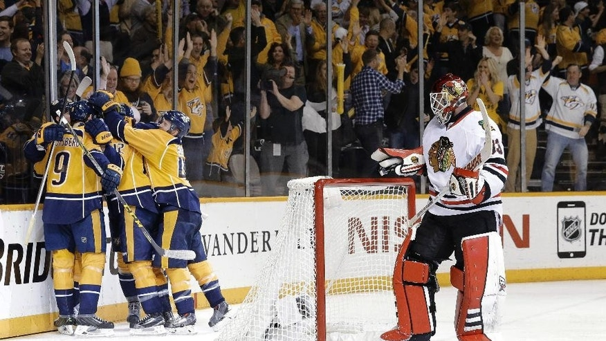 Nashville Predators center Filip Forsberg (9), of Sweden, celebrates with teammates after scoring a goal against Chicago Blackhawks goalie Scott Darling (33) during the third period of Game 5 of an NHL Western Conference hockey playoff series Thursday, April 23, 2015, in Nashville, Tenn. (AP Photo/Mark Humphrey)