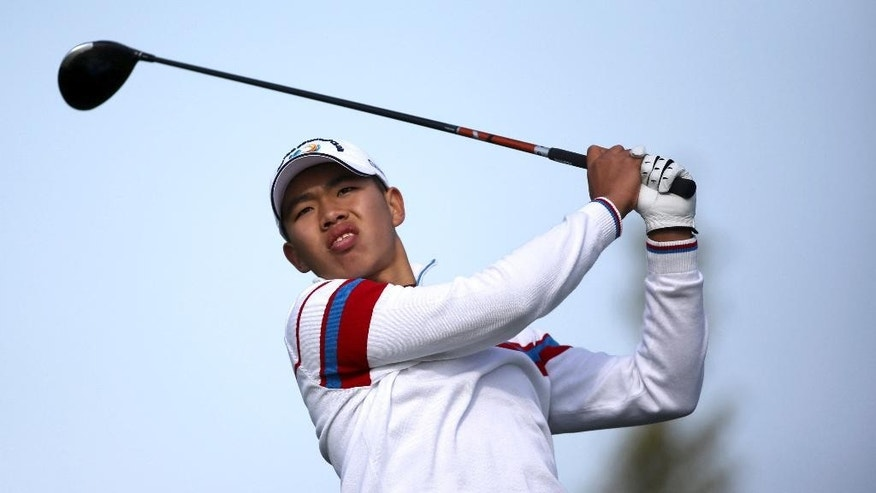 FILE - In this Oct. 24, 2013 file photo, China's Guan Tianlang watches his tee shot during the first day of the Asia-Pacific Amateur Championship golf tournament at Nanshan International Golf Club in Longkou city, east China's Shandong province. In 2103, 14-year-old Guan made history by becoming the youngest player ever to make the cut at the Masters. On Friday, April 24, 2015, before far fewer spectators, the now-16-year-old Chinese golfer completed his second round at the Volvo China Open at 4-over 147 and will miss the weekend. Guan has had a quiet couple of years since his star turn at Augusta National. He still makes a sartorial statement on the course in Shanghai, China, but he's no longer chased by crowds of fans or reporters. He's still developing his game at junior tournaments and going to school part-time. (Chinatopix via AP, File) CHINA OUT