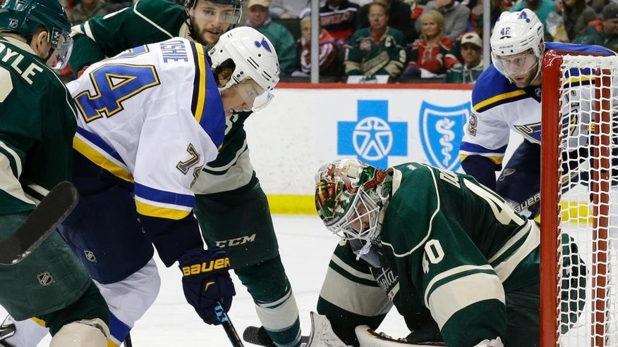 Minnesota Wild goalie Devan Dubnyk (40) tries to cover the puck in front of St. Louis Blues right wing T.J. Oshie (74) during the second period of Game 4 of an NHL hockey first-round playoff series game in St. Paul, Minn., Wednesday, April 22, 2015. (AP Photo/Ann Heisenfelt)