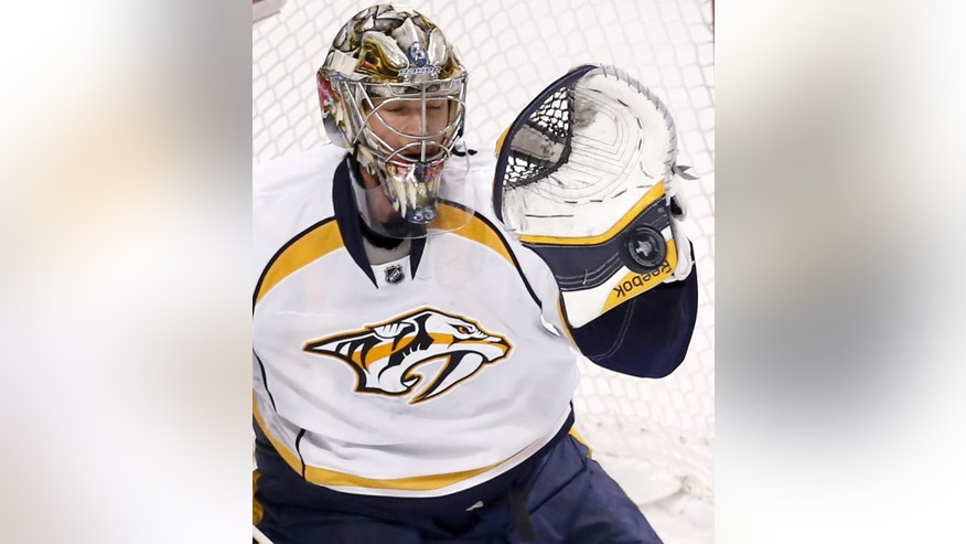 Nashville Predators goalie Pekka Rinne makes a glove save during the third period in Game 4 of an NHL Western Conference hockey playoff series against the Chicago Blackhawks, Tuesday, April 21, 2015, in Chicago. (AP Photo/Charles Rex Arbogast)