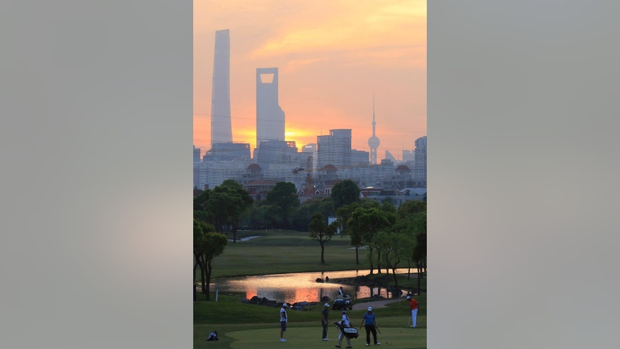 Golfers play on the 9th hole, with the city skyline in the background, during the first round of the Volvo China Open in Shanghai, China, Thursday April 23, 2015.  (AP Photo)