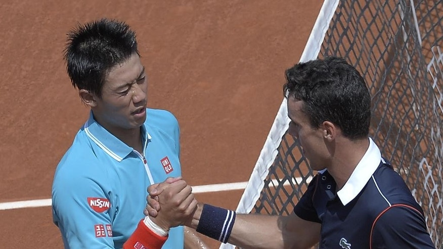 Kei Nishikori of Japan, left, shakes hands with Roberto Bautista of Spain, after winning the match during the Barcelona open tennis tournament in Barcelona, Spain, Friday, April 24, 2015. (AP Photo/Manu Fernandez)
