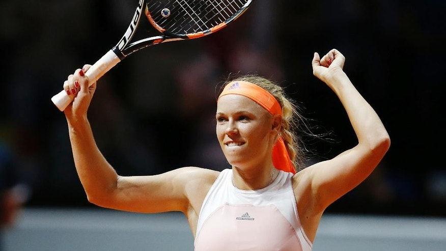 Denmark's Caroline Wozniacki reacts after beating Romania's Simona Halep in their semifinal match at the Porsche Grand Prix tennis tournament in Stuttgart, Germany, Saturday, April 25, 2015. (AP Photo/Michael Probst)
