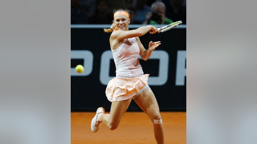Denmark's Caroline Wozniacki hits a forehand against Romania's Simona Halep during their semifinal match at the Porsche Grand Prix tennis tournament in Stuttgart, Germany, Saturday, April 25, 2015. (AP Photo/Michael Probst)
