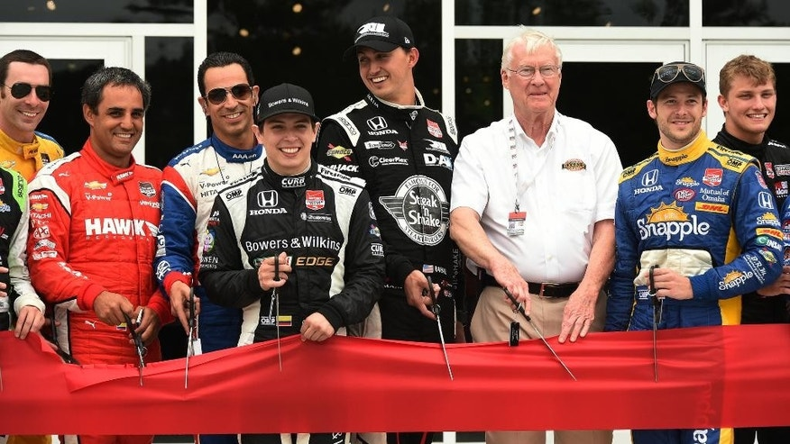 Barber Motorsports Park owner George Barber, third from right, is flanked by IndyCar drivers during the ribbon cutting ceremony for the new pedestrian bridge at the track at the IndyCar Indy Grand Prix of Alabama auto race, Saturday, April 25, 2015, in Birmingham, Ala. (Joe Songer/AL.com via AP) MAGS OUT; MANDATORY CREDIT