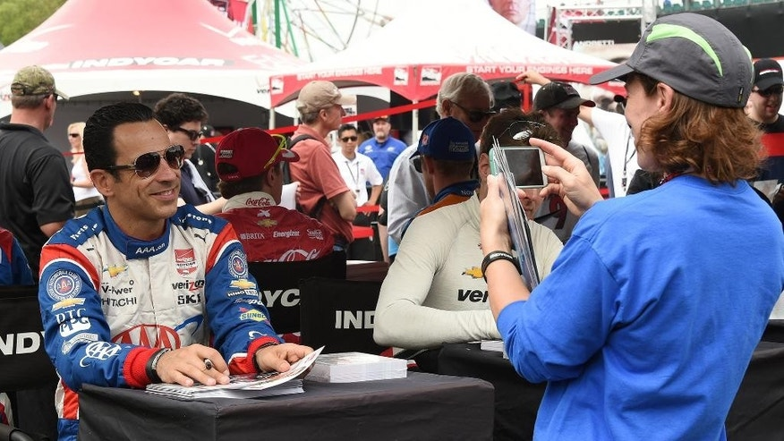 A race fan takes a photo of driver  Helio Castroneves at the IndyCar Indy Grand Prix of Alabama auto race at Barber Motorsports Park, Saturday, April 25, 2015, in Birmingham, Ala. (Joe Songer/AL.com via AP) MAGS OUT; MANDATORY CREDIT