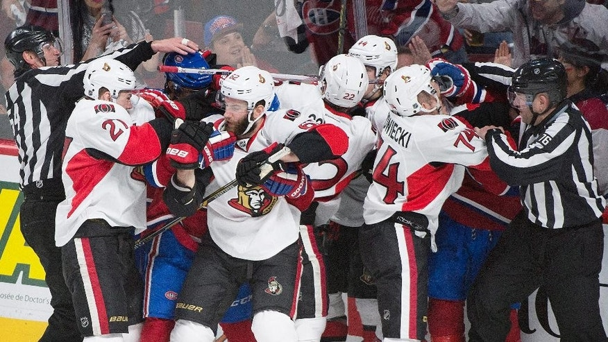 Players from the Ottawa Senators and the Montreal Canadiens fight during the third period of Game 5 of a first-round NHL hockey playoff series, Friday, April 24, 2015, in Montreal. (Graham Hughes/The Canadian Press via AP)