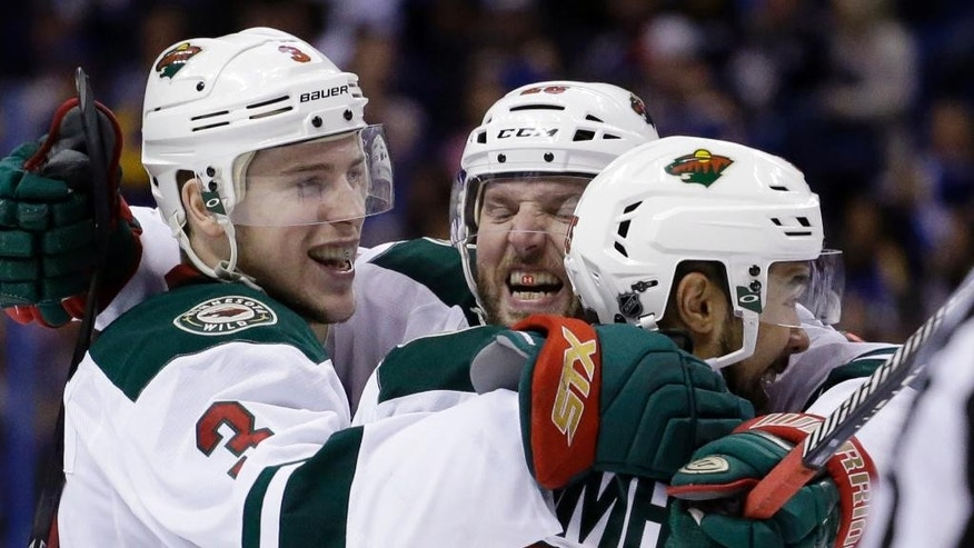 Minnesota Wild's Charlie Coyle, left, is congratulated by teammates Thomas Vanek, of Austria, and Matt Dumba, right, after scoring during the third period in Game 5 of an NHL hockey first-round playoff series against the St. Louis Blues, Friday, April 24, 2015, in St. Louis. The Wild won 4-1. (AP Photo/Jeff Roberson)