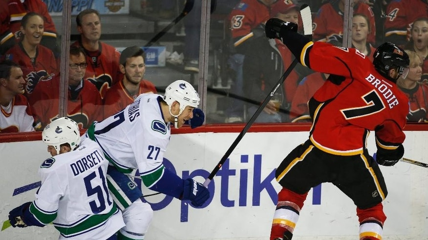 Vancouver Canucks' Derek Dorsett, left, misses his check on Calgary Flames TJ Brodie, right, and collides with teammate Shawn Matthias during the second period of Game 6 of a first-round NHL hockey playoff series, Saturday, April 25, 2015, in Calgary, Alberta. (Jeff McIntosh/The Canadian Press via AP)