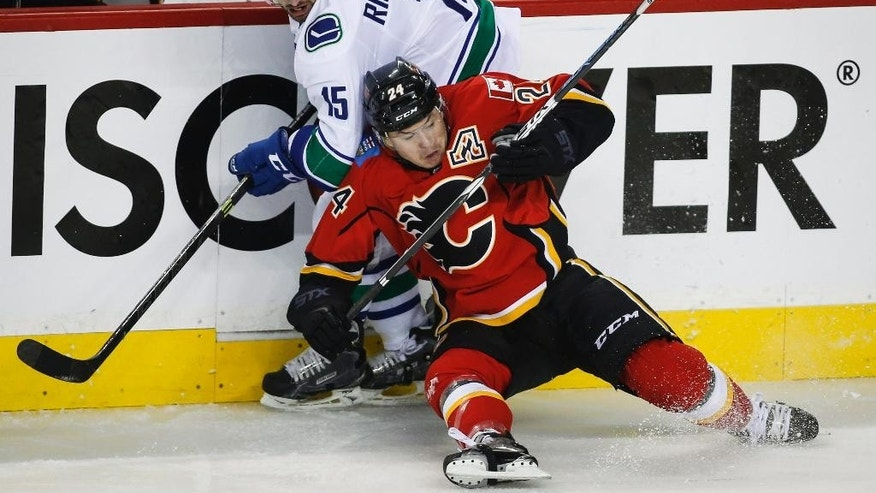 Vancouver Canucks Brad Richardson, left, squeezes past Calgary Flames Jiri Hudler, from the Czech Republic, during the first period of Game 6 of a first-round NHL hockey playoff series, Saturday, April 25, 2015, in Calgary, Alberta. (Jeff McIntosh/The Canadian Press via AP)