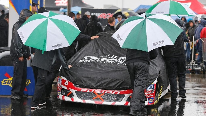 The crew for Trevor Baine (6) pushes his car to the inspection station as rain falls at Richmond International Raceway in Richmond, Va., Saturday, April 25, 2015.  The Sprint Cup Series auto race is scheduled for Saturday night ,but the weather reports predict rain all evening.  (AP Photo/Steve Helber)