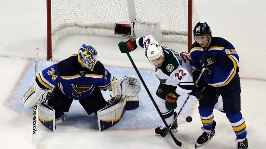 Minnesota Wild's Nino Niederreiter (22), of Switzerland, keeps his eye on a loose puck as St. Louis Blues goalie Jake Allen, left, and Kevin Shattenkirk defend during the second period in Game 5 of an NHL hockey first-round playoff series, Friday, April 24, 2015, in St. Louis. (AP Photo/Jeff Roberson)