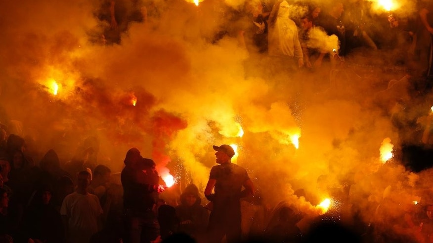 Partizan soccer fans light torches during a Serbian National soccer league derby match between Red Star and Partizan, in Belgrade, Serbia, Saturday, April 25, 2015. Thousands of riot policemen have been deployed throughout Belgrade to prevent possible violence during a derby match between bitter rivals Red Star and Partizan. (AP Photo/Darko Vojinovic)
