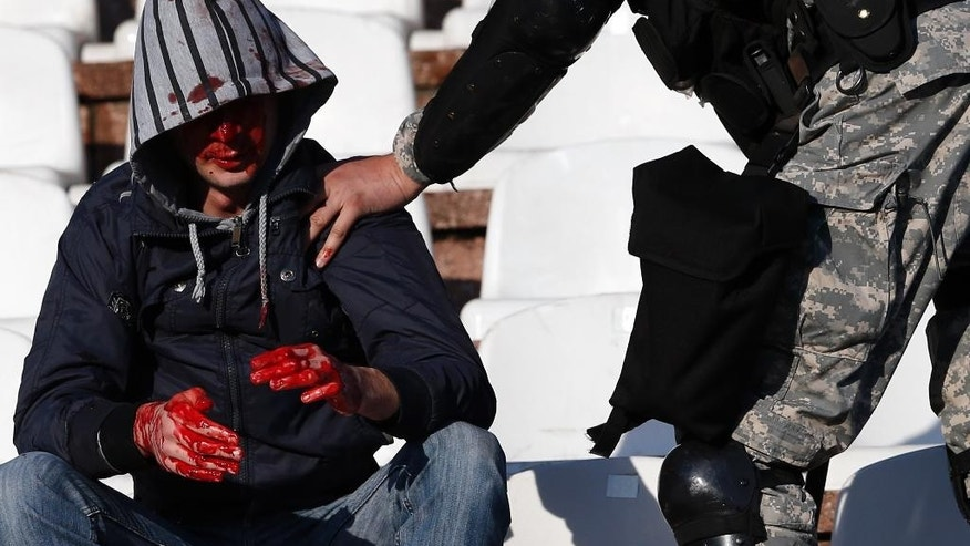 A Serbian riot police officer arrests an injured soccer fan during a Serbian National soccer league derby match between Partizan and Red Star in Belgrade, Serbia, Saturday, April 25, 2015. Thousands of riot policemen have been deployed throughout Belgrade to prevent possible violence during a derby match between bitter rivals Red Star and Partizan. (AP Photo/Darko Vojinovic)
