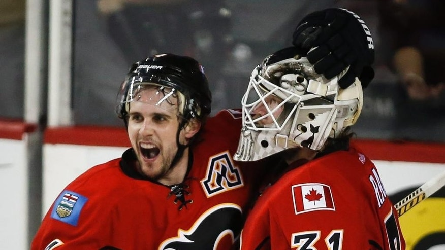 Calgary Flames goalie Karri Ramo, right, from Finland, and teammate Kris Russell celebrate after Game 6 of a first-round NHL hockey playoff series against the Vancouver Canucks, Saturday, April 25, 2015, in Calgary, Alberta. The Flames won 7-4 and took the series. (Jeff McIntosh/The Canadian Press via AP)