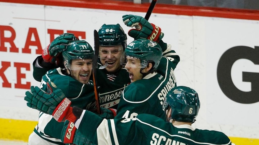 Minnesota Wild left wing Zach Parise, left, celebrates with teammates center Mikael Granlund (64), of Finland, defenseman Jared Spurgeon, and defenseman Marco Scandella (6) after Parise's goal on St. Louis Blues goalie Jake Allen during the first period of Game 6 of an NHL hockey first-round playoff series in St. Paul, Minn., Sunday, April 26, 2015. (AP Photo/Ann Heisenfelt)