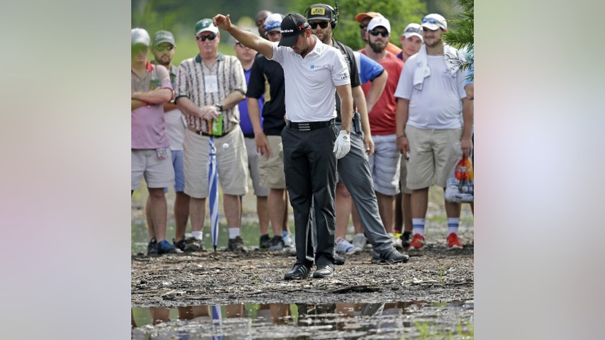 Jason Day, of Australia, takes a drop in the mud off the 15th fairway during the final round of the PGA Zurich Classic golf tournament at TPC Louisiana in Avondale, La., Sunday, April 26, 2015. Day finished the tournament tied for fourth place. (AP Photo/Gerald Herbert)