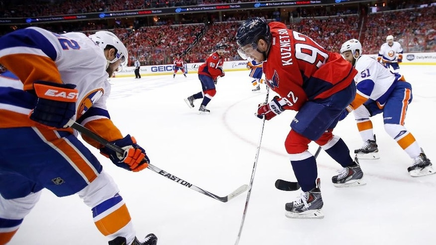 Washington Capitals center Evgeny Kuznetsov (92), from Russia, works the puck with New York Islanders left wing Josh Bailey (12) defending, during the first period of Game 7 in the first round of the NHL hockey Stanley Cup playoffs, Monday, April 27, 2015, in Washington. (AP Photo/Alex Brandon)