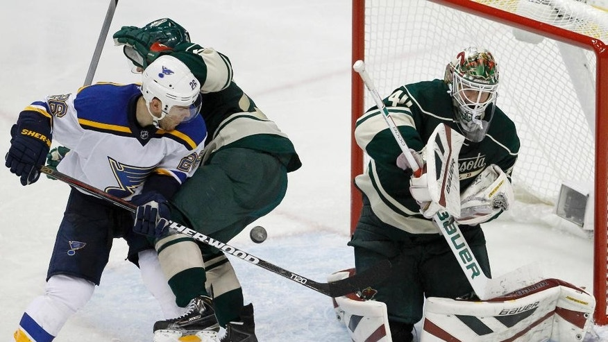 Minnesota Wild goalie Devan Dubnyk, right,  deflects a shot in front of St. Louis Blues center Paul Stastny, left, and Wild defenseman Jonas Brodin, center, during the third period of Game 6 of an NHL hockey first-round playoff series in St. Paul, Minn., Sunday, April 26, 2015. The Wild won 4-1 to win the series and advance to the second round. (AP Photo/Ann Heisenfelt)